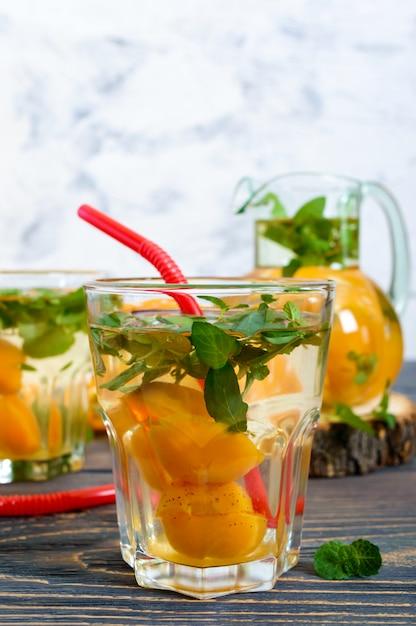 Zomer koude drankjes. heerlijk verfrissend drankje met abrikoos en munt in glazen op een houten tafel. compote van fruit. selectieve aandacht. Premium Foto