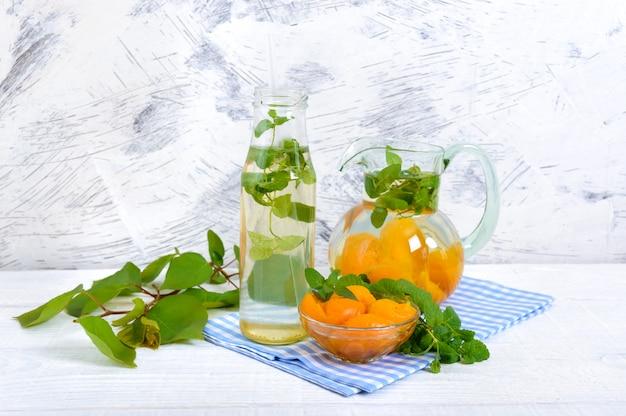 Zomer koude drankjes. heerlijk verfrissend drankje met abrikoos en munt in glazen op een witte houten achtergrond. compote van fruit. Premium Foto