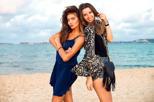 Zomer levensstijl mode portret van jonge vrouwen in stijlvolle outfits, wandelen in de buurt van de oceaan, positieve stemming, vintage getinte kleuren. Gratis Foto