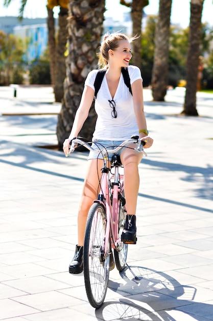 Zomer levensstijl portret van gelukkig vreugdevolle blonde hipster meisje, sportieve fit dagen, vintage roze fiets rijden, reizen met rugzak op exotisch land, plezier buitenshuis, palmen, park, natuur. Gratis Foto
