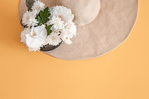Zomer met verse witte bloemen en een grote rieten hoed, op stevig. Gratis Foto