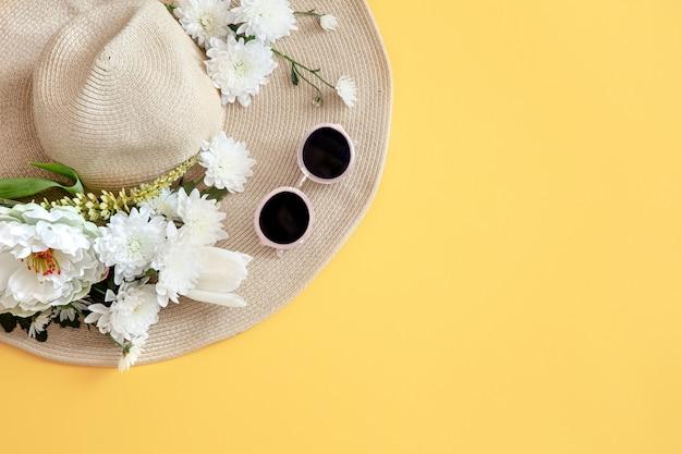 Zomer met witte bloemen en een rieten hoed met zonnebril Gratis Foto