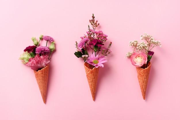 Zomer minimaal concept. roomijskegel met roze bloemen en bladeren op punchy pastelkleurachtergrond. Premium Foto