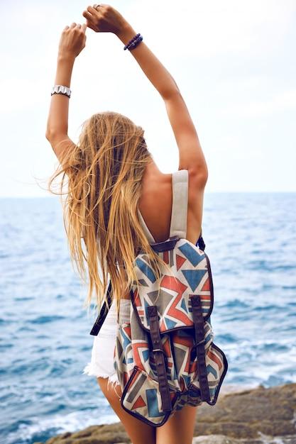 Zomer mode portret ga jonge vrouw reizen met rugzak in de zomer, poseren in de buurt van de oceaan op regenachtige dag, wind droevige stemming. Gratis Foto
