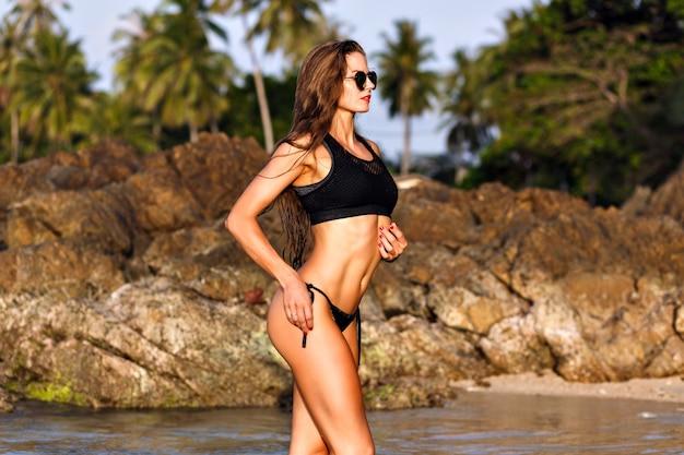 Zomer mode portret van mooie vrouw die zich voordeed op het strand, natte mode look, fit lichaam, zwarte bikini, slank fitness lichaam Gratis Foto