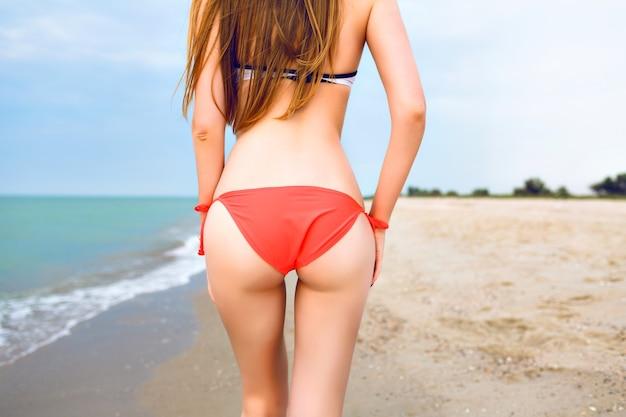 Zomer portret van jonge vrouw poseren terug in het slanke lichaam van het strand, strandvakantie, heldere bikini dragen. Gratis Foto