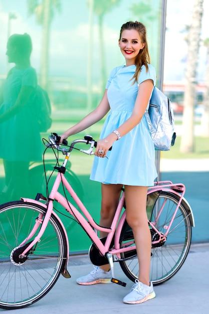 Zomer positieve levensstijl portret van hipster mooie blonde vrouw, speelse bui, fiets rijden op barcelonetta, roze vintage pastel stijl, korte blauwe jurk, zilveren rugzak Gratis Foto