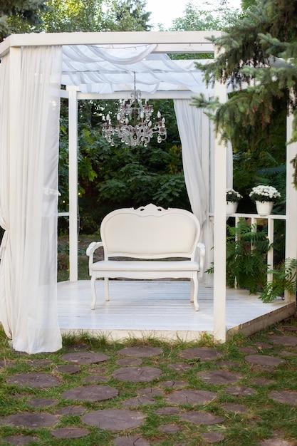 Zomer prieel met witte gordijnen. alkoof is er terras waarop een witte bank in provençaalse of rustieke stijl. Premium Foto