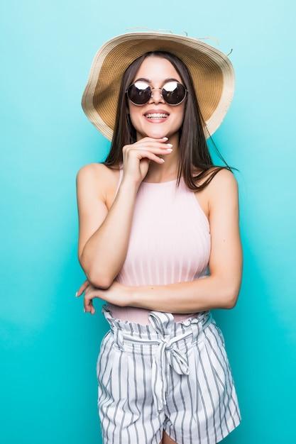 Zomer reizen vrouw in hoed en zonnebril klaar voor feestreis en feest geïsoleerd op blauwe muur. aantrekkelijk glimlachend meisje dat aan vakantie denkt. zomerstemming. Gratis Foto