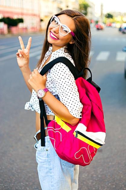 Zomer stad portret van stijlvolle tiener girt, alleen reizen met rugzak, mooie dag hebben in nieuwe stad, genieten van haar vakantie, rugzak, hipster bril en casual look, vreugde, emoties dragen Gratis Foto