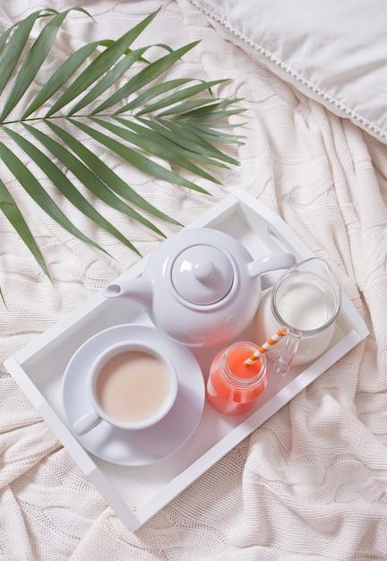 Zomer tropisch ontbijt met kopje thee, theepot en verfrissend exotisch sap in een fles met stro op een wit dienblad onder het palmblad Premium Foto