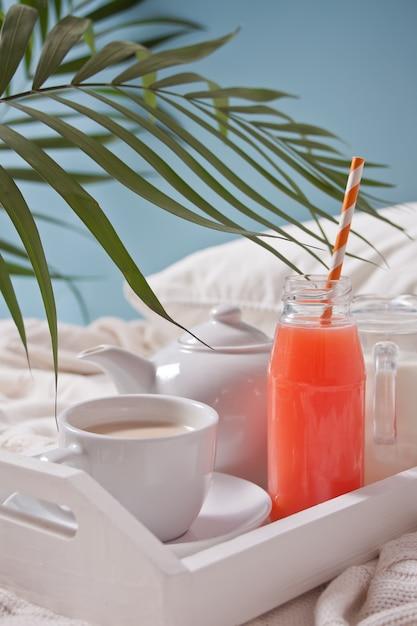 Zomer tropisch ontbijt met kopje thee, theepot en verfrissend exotisch sap Premium Foto