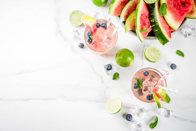 Zomer verfrissing drankje, watermeloen en bosbessen limonade cocktail met limoen, munt en ijsblokjes, witte marmeren achtergrond Premium Foto