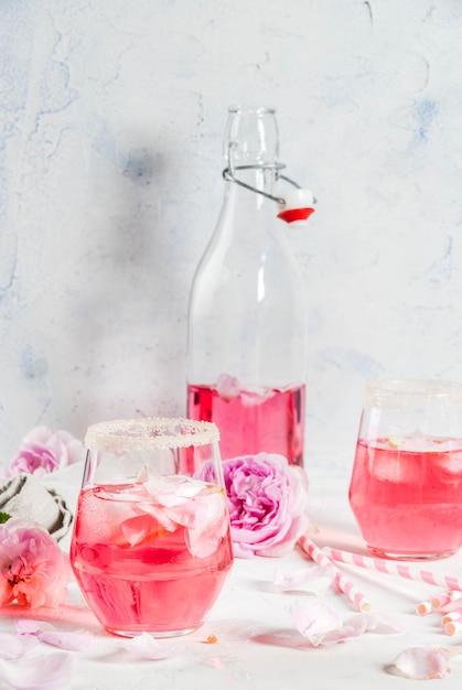 Zomer verfrissing drankjes. lichtroze rozencocktail, met rose wijn, theeblaadjes, citroen. op een witte stenen betonnen tafel. met gestreepte roze buisjes, bloemblaadjes en roze bloemen. kopieer ruimte Premium Foto