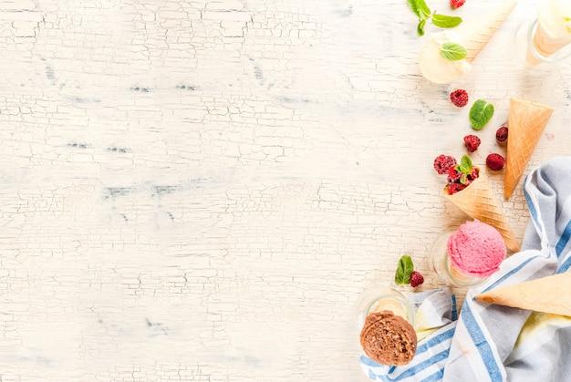Zomer zoete bessen en desserts, verschillende ijssmaak in kegels roze (framboos), vanille en chocolade met munt op licht beton Premium Foto