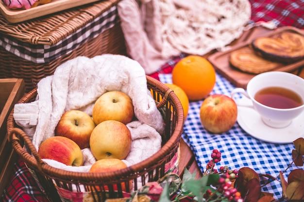 Zomerpicknick met een mand met voedsel op deken in het park. Premium Foto