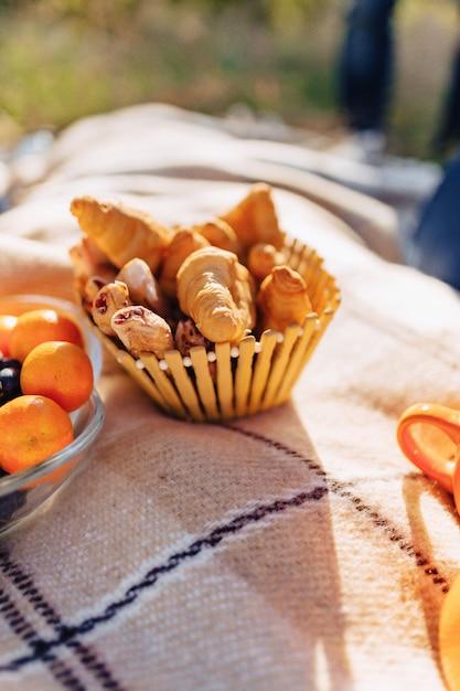 Zomerpicknick op een kleed met fruit, wijn en thee, kopjes, croissants en snoepdetails Premium Foto