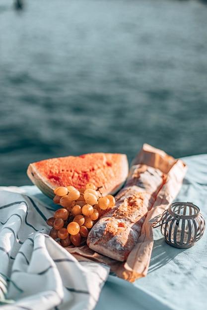 Zomerpicknick op een strand. verse watermeloen, frans stokbrood en druiven op een deken. Premium Foto