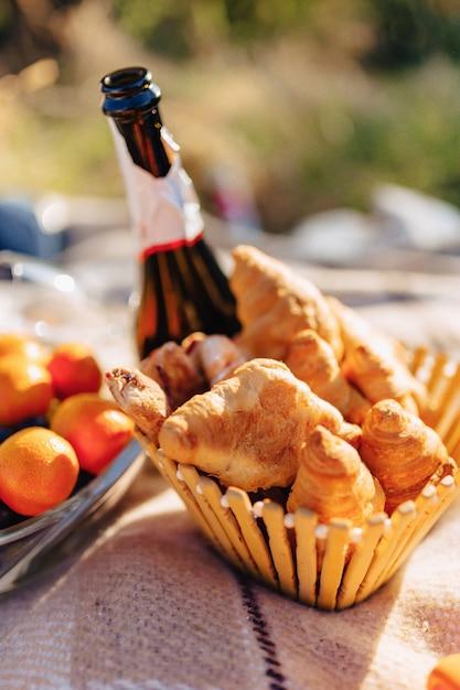 Zomerpicknick op een tapijt met fruit, wijn en thee, kopjes, croissants en zoetigheden Premium Foto
