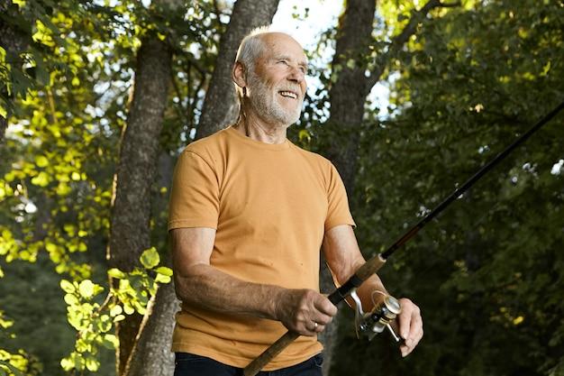 Zomerse foto van knappe energieke actieve ongeschoren senior man die met pensioen gaat mooie zomerochtend buitenshuis doorbrengen, vis vangen met behulp van een hengel, met vrolijke, vrolijke gezichtsuitdrukking Gratis Foto