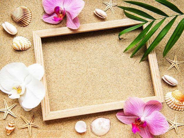 Zomerstranddecoratie: frame met orchideeën, schelpen en zeesterren op een zandoppervlak Premium Foto
