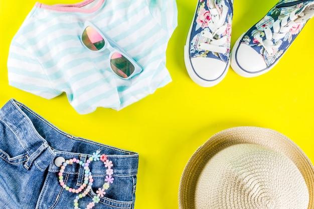 Zomervakantie concept, zomers kinderkleding set - kinder shorts, t-shirt, hoed, zonnebril, armband ketting, sneakers, fel gele tafel plat lag Premium Foto