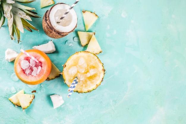 Zomervakantie drankje concept, stel verschillende tropische cocktails of sappen in ananas, grapefruit en kokosnoot met ijs, lichtblauw beton Premium Foto