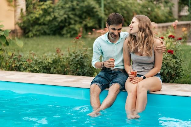 Zomervakantie, mensen, romantiek, dating concept, koppel mousserende wijn drinken terwijl u geniet van tijd samen bij het zwembad Gratis Foto