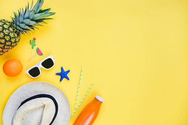 Zomervakantie strohoed, witte zonnebril, tropisch fruit, vers sap en cocktailaccessoires over geel Premium Foto