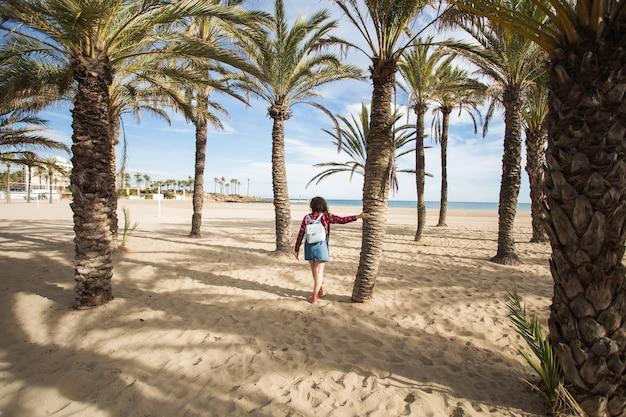 Zomervakantie, vakanties en reizen concept - mooie jonge vrouw onder takken van de palmbomen aan zee. Premium Foto