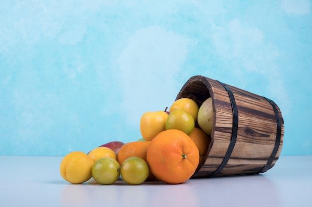 Zomervruchten mengen uit een houten emmer op blauw. Gratis Foto