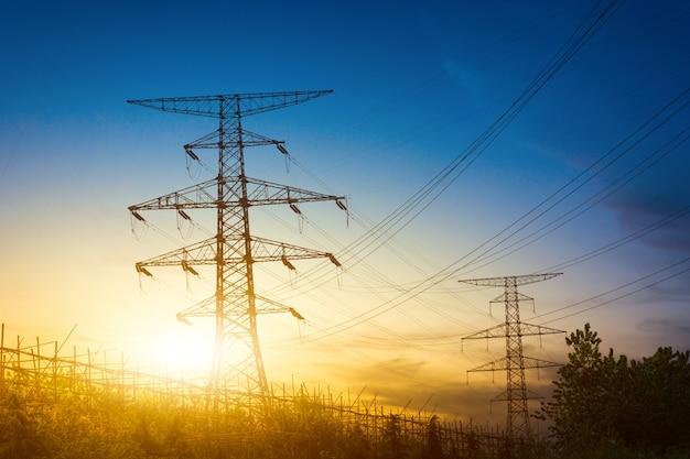 Zon instelling achter het silhouet van elektriciteitspylonen Gratis Foto