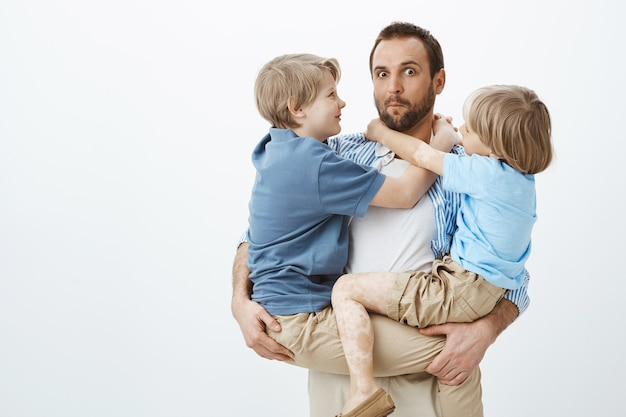 Zonen maken misbruik van een liefdevolle en zorgzame vader. portret van clueless grappige europese vader die kinderen op handen houdt en cluelessly staart Gratis Foto