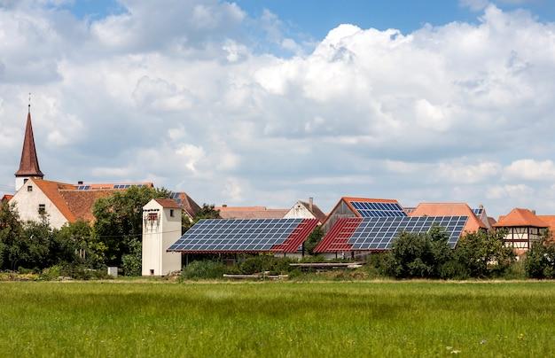 Zonne aangedreven huizen in een landelijk dorp in duitsland. zonnepanelen op het dak als alternatieve energiebron. Premium Foto