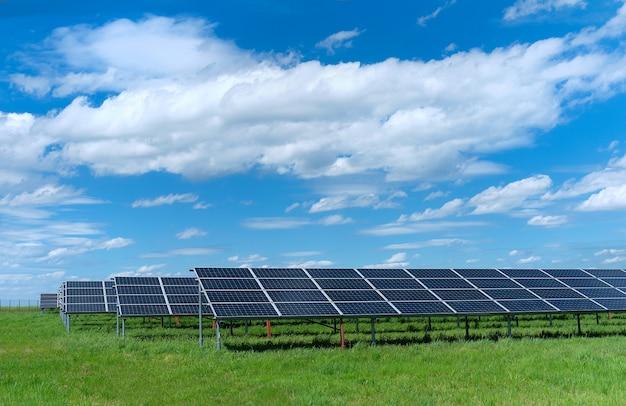 Zonne-energiecentrale, blauwe zonnepanelen op groen grasveld onder blauwe hemel met wolken Premium Foto