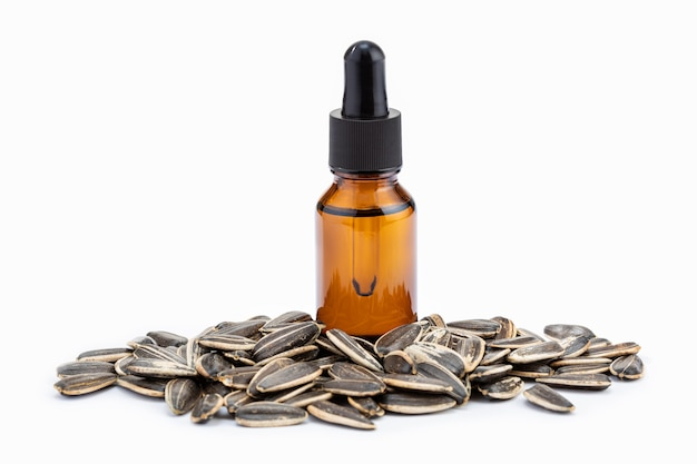 Zonnebloem etherische olie in fles en zaden geïsoleerd op wit Premium Foto