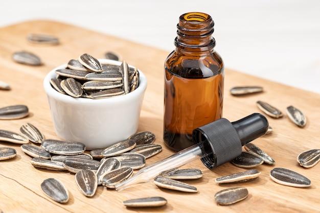 Zonnebloem etherische olie in glazen fles met pipet op houten tafel Premium Foto