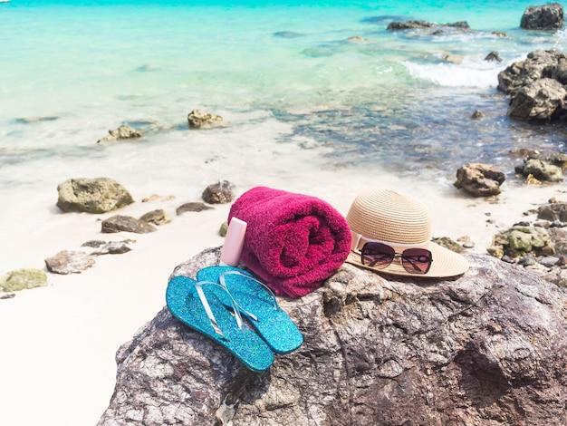 Zonnebrandcrème, hoed, glas, schoenen op steen met zee achtergrond. zomer- en vakantieconcept. Premium Foto