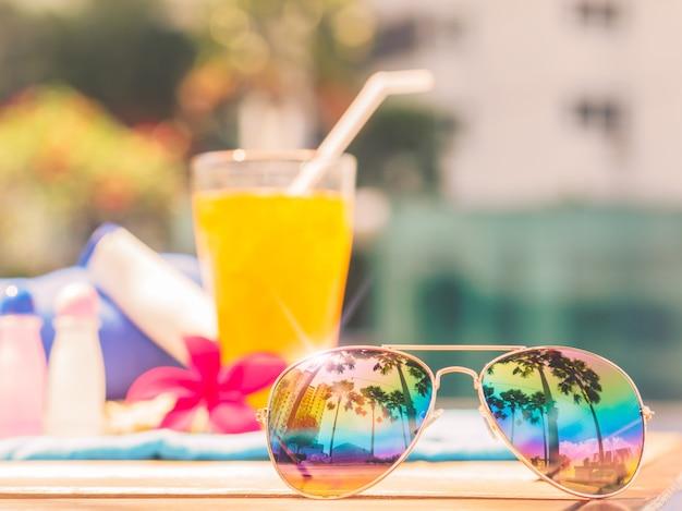 Zonnebrillen, shampoo, lotion en sinaasappelsap aan de rand van het zwembad Premium Foto