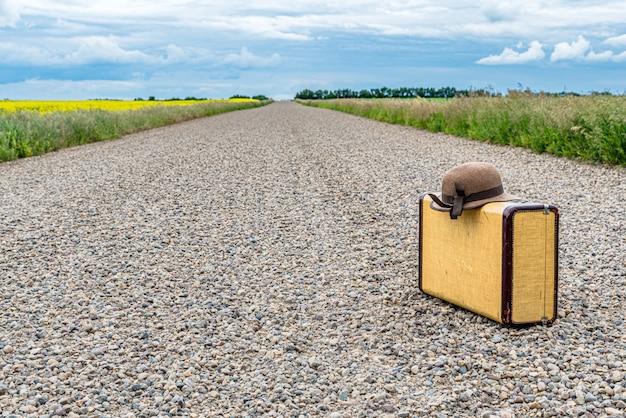 Zonnehoed en vintage koffer op een landweg op de prairies Premium Foto