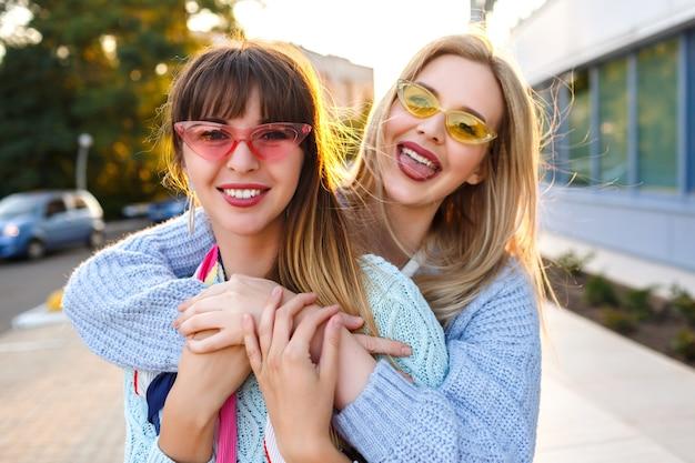 Zonnig positief portret van gelukkig lesbisch koppel genieten van tijd samen, zonnige kleuren, trendy pastel outfits en zonnebrillen, lente herfst tijd, prettige vakantie in europa. Gratis Foto