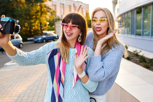 Zonnige buiten portret of twee vrolijke grappige hipster vrouw selfie maken op vintage camera pastel kleuren trendy truien en glazen dragen, beste vrienden zuster samen plezier. Gratis Foto