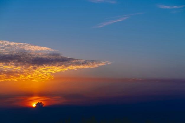 Zonnige glans op wolken. prachtige levendige dageraad. mooie rustige oranje zonsondergang. Premium Foto