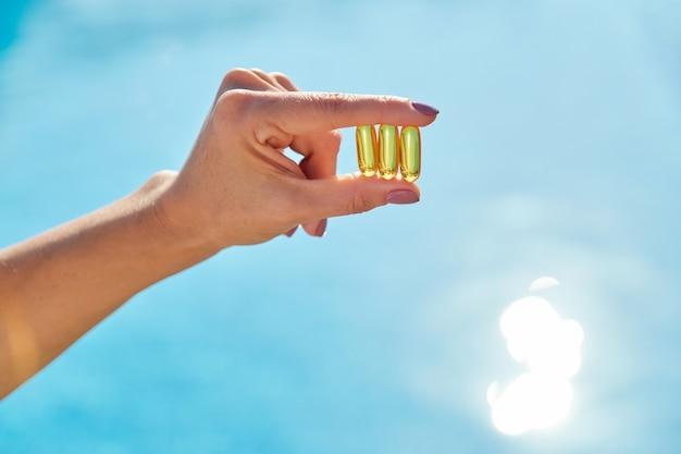 Zonnige gouden vitamine d-oliecapsules omega-3 in vrouwenhand Premium Foto