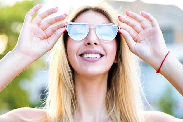 Zonnige lente zomer portret van gelukkige blonde vrouw genieten van mooie warme dag glimlachend en sluit haar ogen, stijlvolle trendy bril, positieve stemming. Gratis Foto