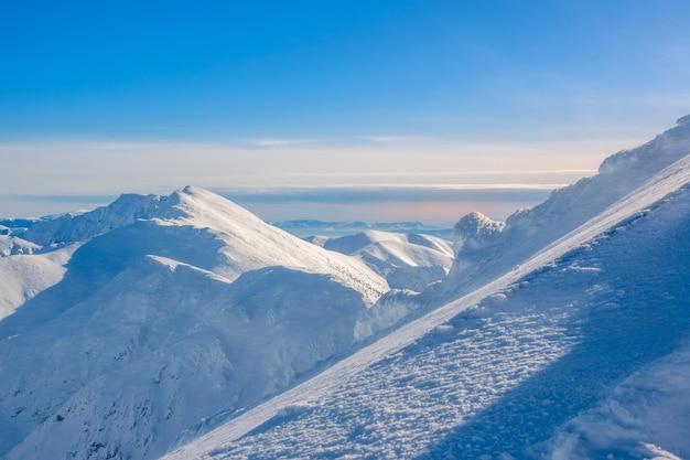 Zonnige winterdag. bergtoppen en blauwe lucht. op de voorgrond daalt een steile skipiste Premium Foto