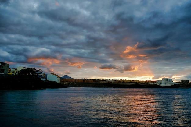 Zonsondergang boven het water onder een bewolkte hemel in canarische eilanden, spanje Gratis Foto