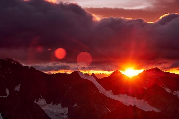 Zonsondergang in bergen. weerspiegeling van rode zon op bergsneeuwpieken en wolken. altai, belukha gebied Premium Foto