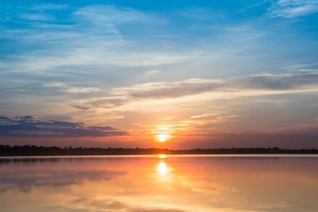 Zonsondergang in het meer. prachtige zonsondergang achter de wolken boven de meer landschap achtergrond. Premium Foto