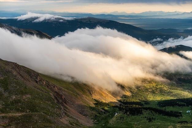 Zonsondergang met bergketens en wolken Gratis Foto